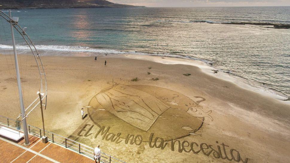 Una gran postal de arena en Las Canteras para denunciar el impacto de las mascarillas abandonadas en el mar